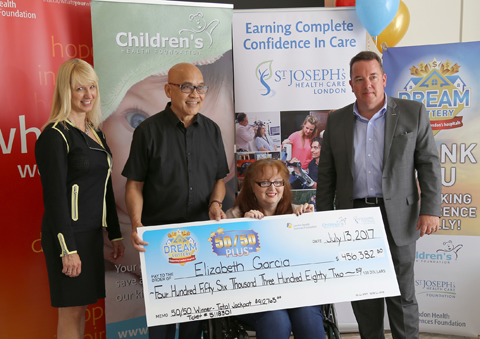 50/50 Plus lottery winner Elizabeth Garcia (seated) and her husband Antonio (second from left) receive their big cheque from LHSF Chief Operating Officer Evelyn Salhani (left) and CHF President & CEO Scott Fortnum (right).