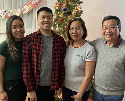 Andy Lam stands and smiles in front of a Christmas tree with his family.