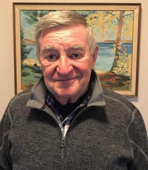 Kind looking male senior standing and smiling in front of a painting.