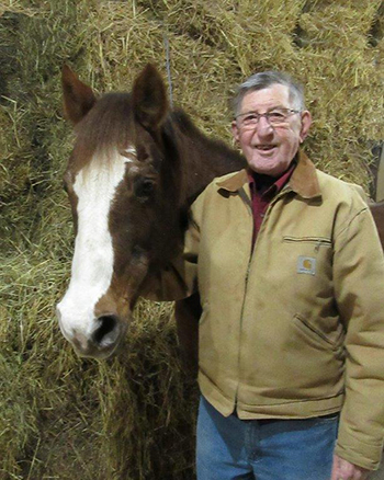 Smiling elderly male standing next to brown horse.