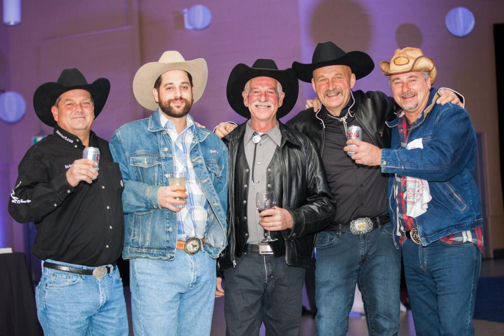 a group of cowboys smile with beer