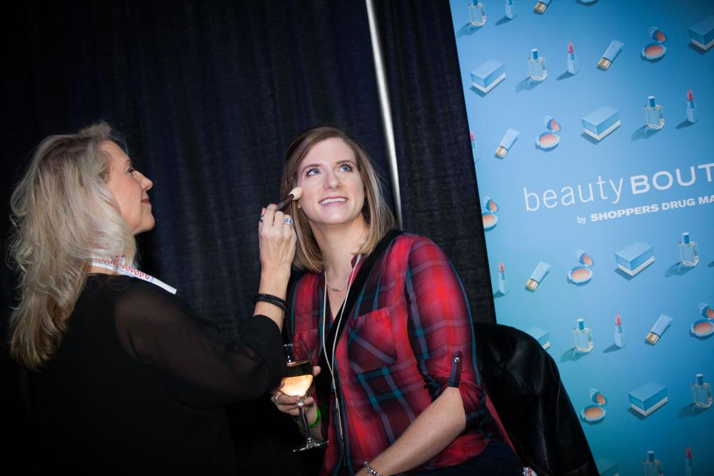 a shoppers shindig attendee gets her make up done by a shoppers beauty expert