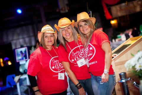 three ladies wearing cowboy hats volunteering at country classic auction