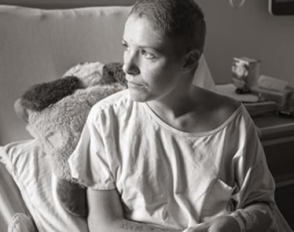 A young woman with a shaved head looks out a window, while sitting in her hospital bed.