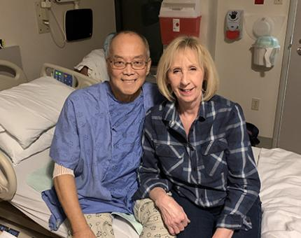 Peter and his wife sitting and smiling on his hospital bed