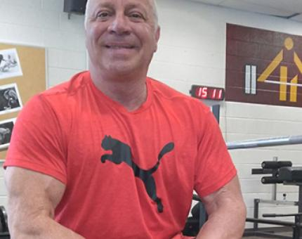 Middle-aged muscle man in red shirt giving a big smile.