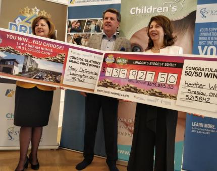 Dream Lottery presidents hold cheques